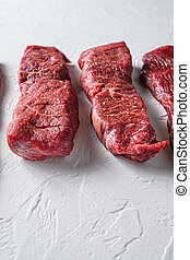 Raw denver steak cut organic meat cut side view close up over white concrete background vertical selective focus