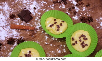 Raw dough for muffins in special paper baking dish sprinkled with chocolate pieces