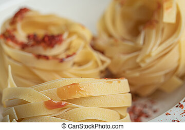 Raw dry nest pasta with red pepper on a white background