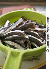 raw fillets of anchovies in a colander