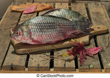 Raw fish carp on a kitchen cutting Board. with red eyes