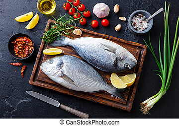 Raw fish Dorado on a wooden cutting board with vegetables, herbs and spices. Black stone background. Top view.