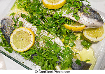 Raw fish with parsley and lemon slice in a glass bowl
