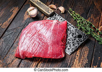 Raw flank beef marbled meat steak on a cleaver. Dark Wooden background. Top view