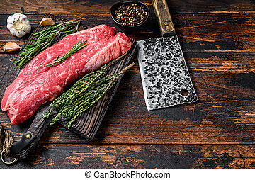 Raw flank beef meat steak on a cutting board with cleaver. Dark wooden background. Top view. Copy space
