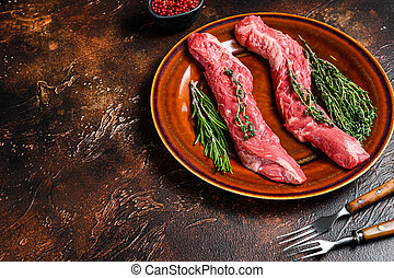 Raw flank beef meat steak on a plate. Dark background. Top view. Copy space