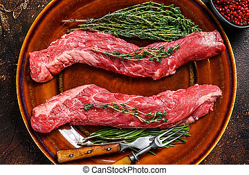 Raw flank beef meat steak on a plate. Dark background. Top view