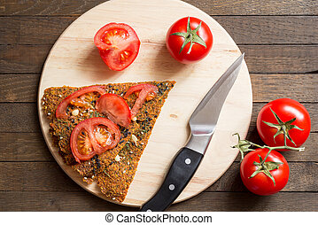Raw food diet concept. Dehydrated raw vegan dry breads, knife and tomatoes on kitchen board.