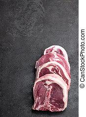 Raw fresh lamb chops on metal background