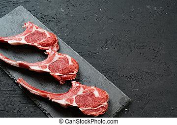 Raw fresh lamb ribs on dark background