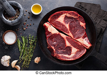 Raw fresh marbled meat Steak Ribeye Black Angus on black marble background. Beef with spices on a dark stone table. Top view