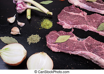 Raw, fresh meat and spices on a black wooden background. Marbled beef with spices