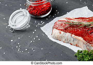 Raw fresh meat t-bone steak with spices on a dark background