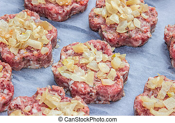 raw fresh pork cutlets with fried onions in the shape of a flower on parchment paper