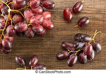 Raw fresh red globe grape on brown wood