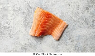 Raw fresh salmon meat placed on gray stone background. Top...