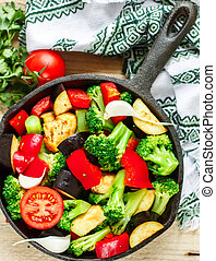 Raw fresh vegetables - broccoli, eggplant, bell peppers, tomatoes, onions, garlic in a cast iron frying pan. Preparation garnish