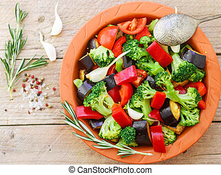 Raw fresh vegetables - broccoli, eggplant, bell peppers, tomatoes, onions, garlic in a clay baking dish