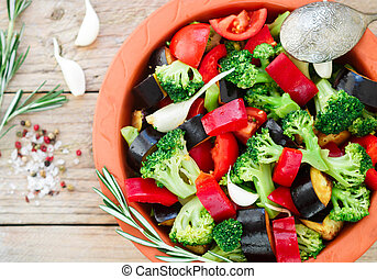 Raw fresh vegetables - broccoli, eggplant, bell peppers, tomatoes, onions, garlic in a clay baking dish. Preparation garnish