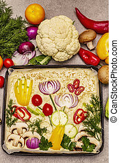 Raw Garden Focaccia. Fresh dough and vegetables, olive oil, greens. Colorful gardenscape, stone concrete background