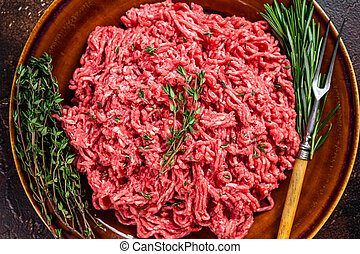 Raw ground beef or veal meat on a rustic plate with herbs. Dark background. Top view