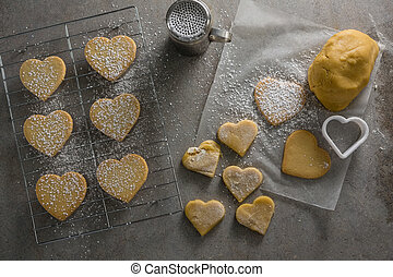 Raw heart shape cookies on baking tray with flour shaker strainer, cookie cutter and wax paper