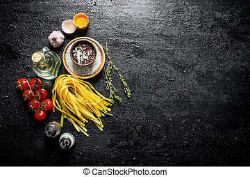 Raw home cooked pasta with spices, egg, oil and tomatoes.