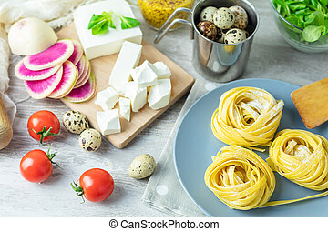 Raw homemade Italian typical pasta linguine noodles on...