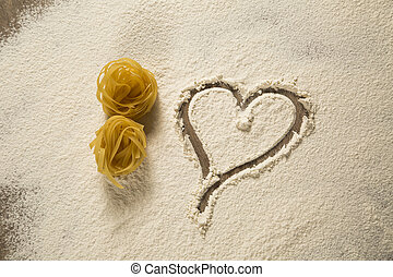 Raw homemade pasta and ingredients for pasta on wooden background with heart