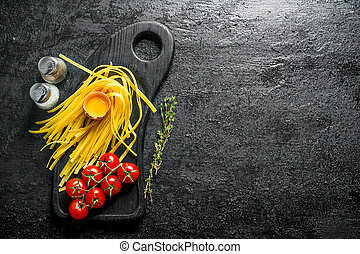 Raw homemade pasta with thyme, egg and tomatoes.