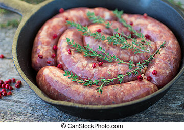 raw homemade sausages frying in a cast iron skillet