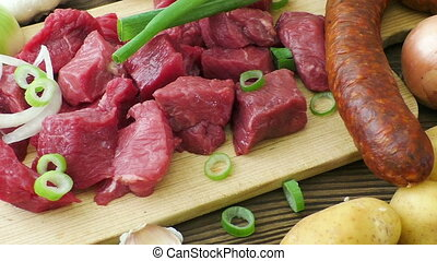 Raw ingredients for stew, goulash or soup. Fresh raw chopped beef on a wooden cutting board with spices and vegetables.