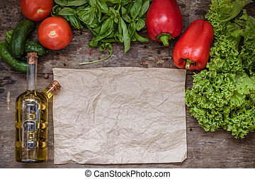 Raw ingredients of salad, tomato, cucumber, pepper, olive oil on a wooden background, top view and blank parchment paper