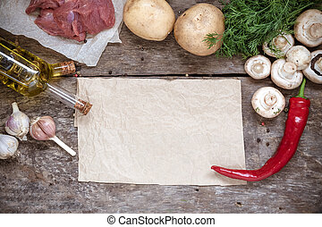 Raw ingredients, potatoes, meat, mushrooms, parsley, oil, pepper, garlic on a wooden background, top view and blank parchment paper