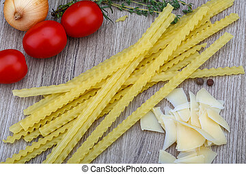 Raw Italian Mafalde pasta with tomatoes, onion and parmesan cheese