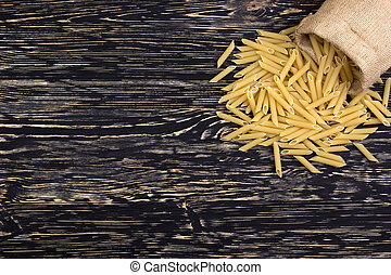 Raw italian pasta on a wooden table.
