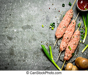 Raw kebab with green onions and tomato sauce.