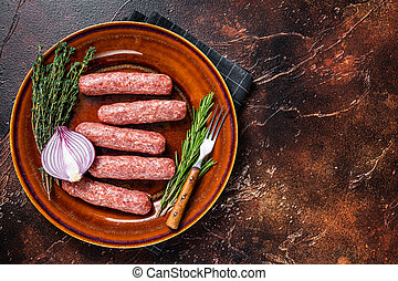 Raw kofta meat kebabs sausages on a plate with herbs. Dark background. Top view. Copy space