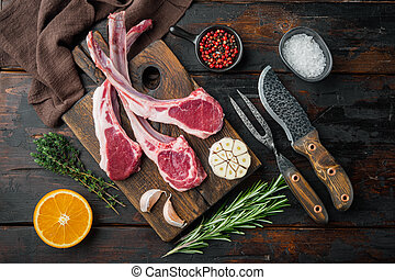 Raw Lamb chops , with ingredients carrot orange, herbs, on old dark wooden table background, top view flat lay