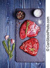 Raw lamb meat on stone board.