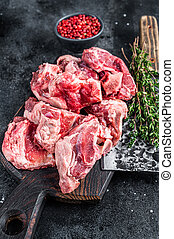 Raw lamb meat stew cuts with bone on wooden butcher board and cleaver. Black background. Top view