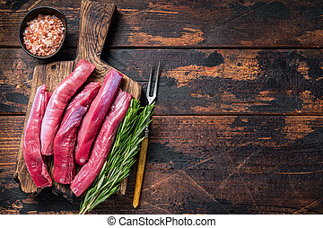 Raw lamb tenderloin Fillet, Mutton Sirloin Meat on wooden board with herbs. Dark wooden background. Top view. Copy space