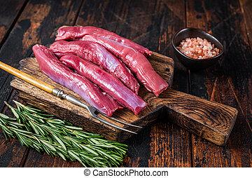 Raw lamb tenderloin Fillet, Mutton Sirloin Meat on wooden board with herbs. Dark wooden background. Top view