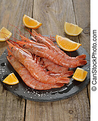 Raw langoustines with lemon on wooden background