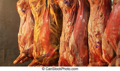 raw meat hanging in a large refrigerator