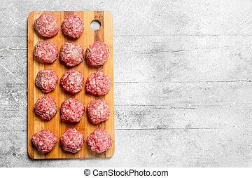 Raw meat meatballs on the Board .