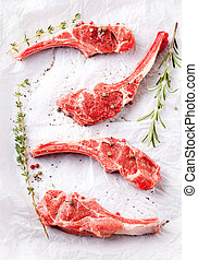 Raw meat, mutton, lamb rack with fresh herbs.