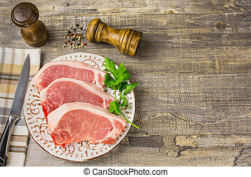 Raw meat on a plate with greens, pepper, Bay leaf, spice kitchen knife  wooden table  napkin Best concept.