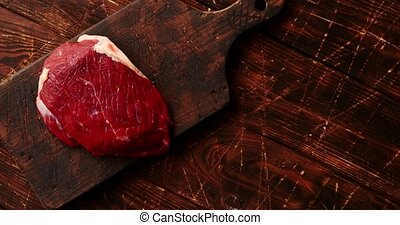 Raw meat on chopping board - From above view of piece of raw...