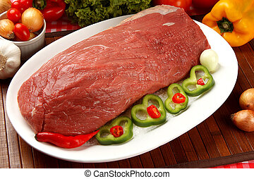 Raw meat on the plate with vegetables